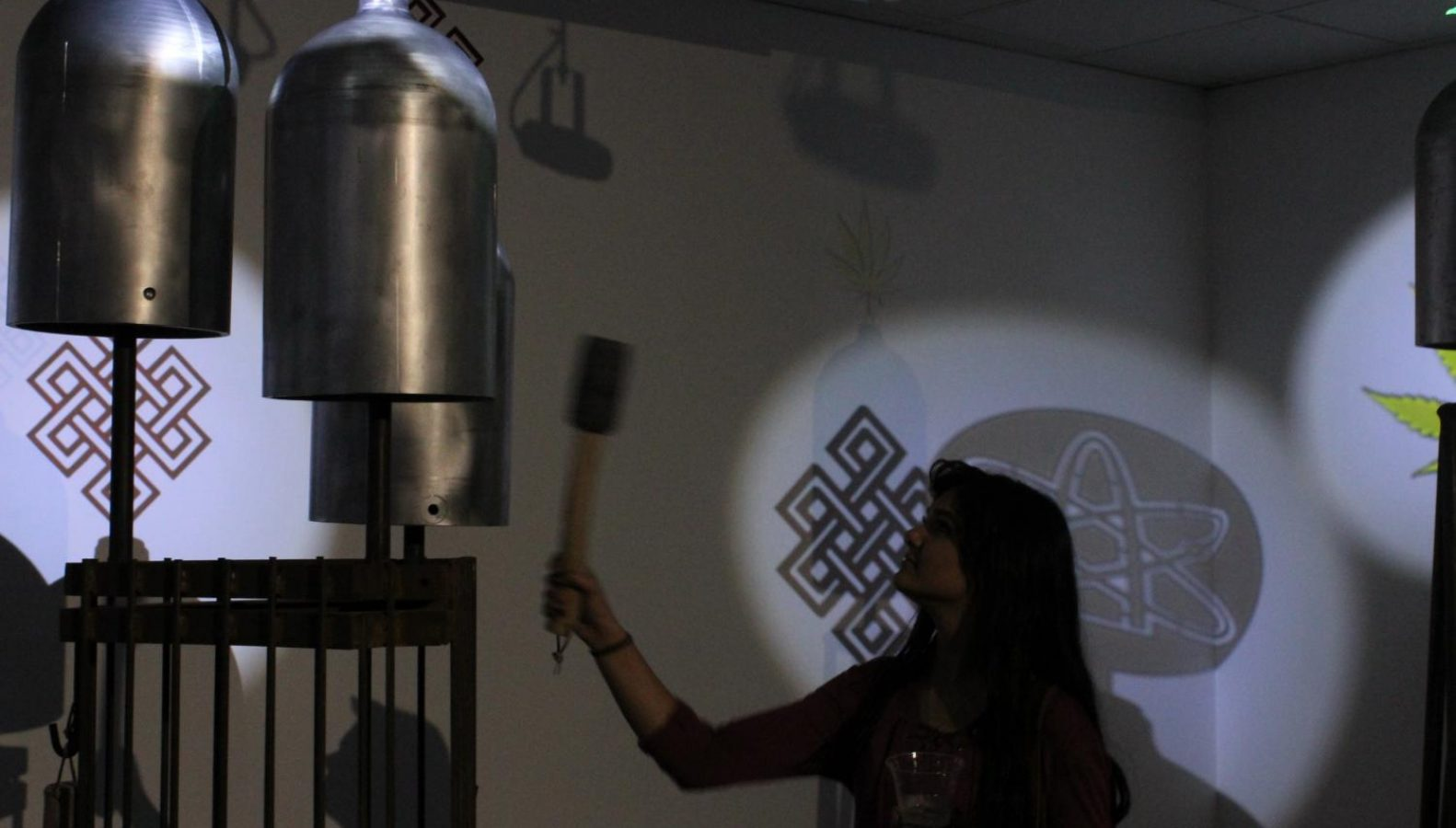 Biochemistry major Meriam Sadat rings one of the bells made from salvaged propane tanks in the exhibit. The bells have a deep and penetrating sound that sent vibrations outward with a meditative hum.  Photo by Nick Minges – The State Hornet