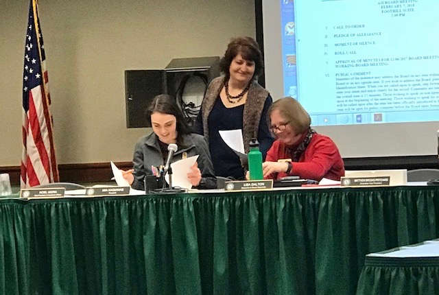 Associated Students, Inc. President Mia Kagianas (left), Lisa Dalton (right) and Gina Curry examine the agena during the ASI meeting on Wednesday. The board voted to remove slates from future election cycles.