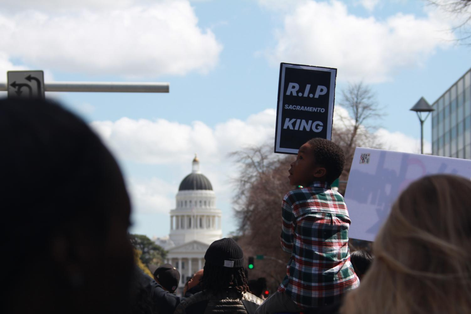 Five-year-old Elias Taylor sits upon his mother Teriah Taylor's shoulders as he holds a sign in a demonstration that took place around downtown Sacramento on Friday, March 23, 2018. Teriah said that she attended the march and brought her son to the demonstration, held in response to the shooting of Stephon Clark by Sacramento Police, because.