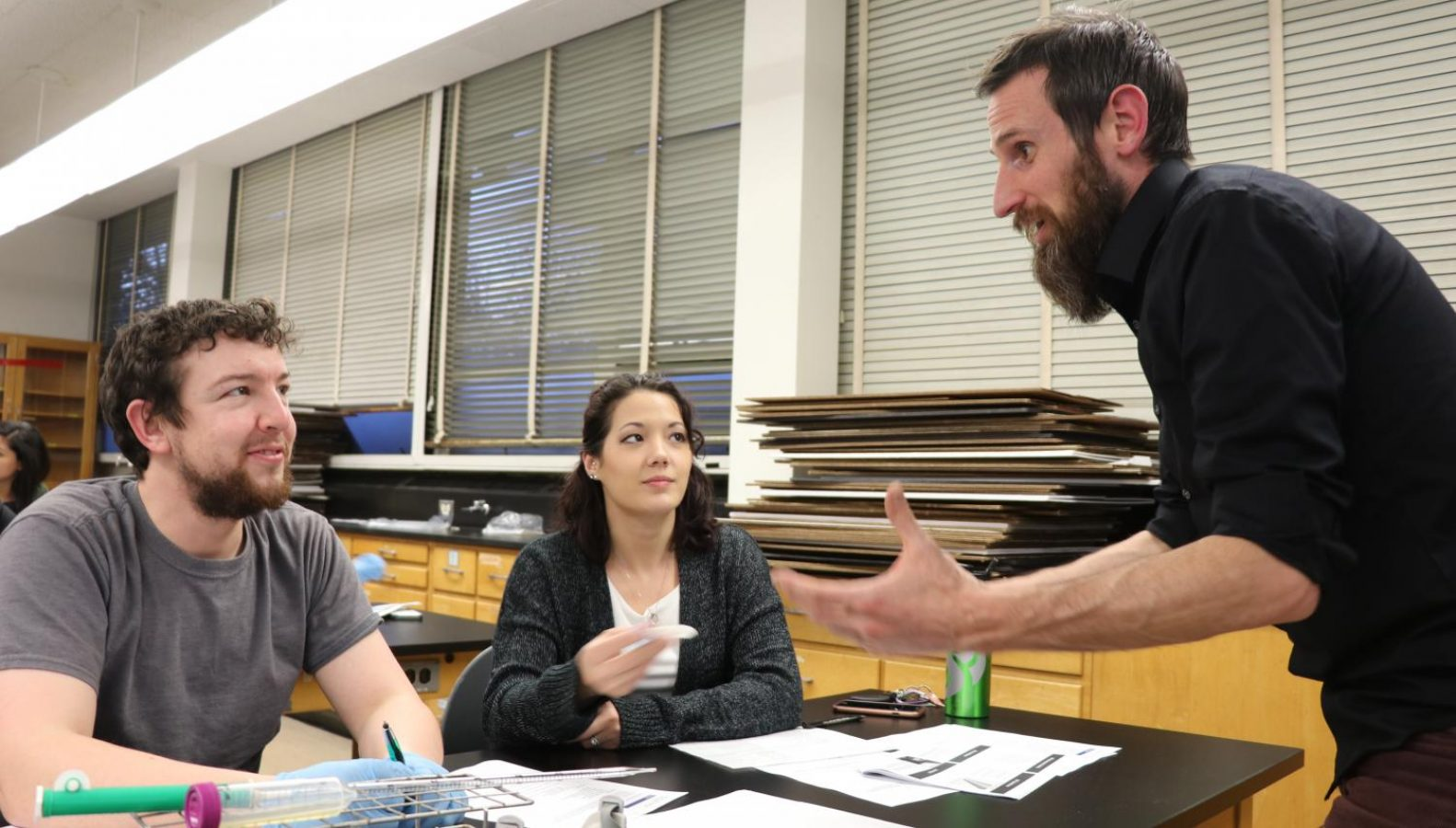 Professor Robert Crawford, right, explains to students Eric McPherson, left, and Laura Givens, center, the process of determining the number of international bitterness units of their beer. This measurement is correlated to to the amount of acids that produce the bitter taste. Photo by Khanlin Rodgers – The State Hornet