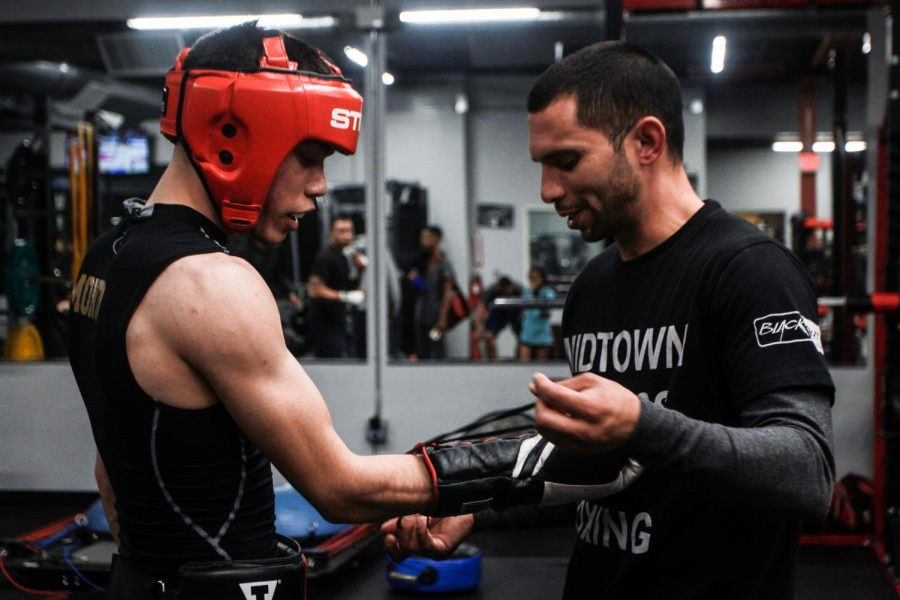 Team+USA+boxer+and+Sacramento+State+student+Kevin+Montano%2C+left%2C+laces+up+his+gloves+with+the+help+of+Andres+Martinez%2C+right%2C+in+preparation+for+a+sparring+match+at+Midtown+Fitness+and+Boxing+in+Sacramento+on+Tuesday%2C+Feb.+20%2C+2018.+With+Montano%27s+home+and+primary+coach+back+in+Concord%2C+Martinez+helps+him+keep+his+skills+sharp+during+the+school+week+by+opening+up+the+gym+to+him+and+setting+up+sparring+bouts+with+other+boxers+in+the+area.+