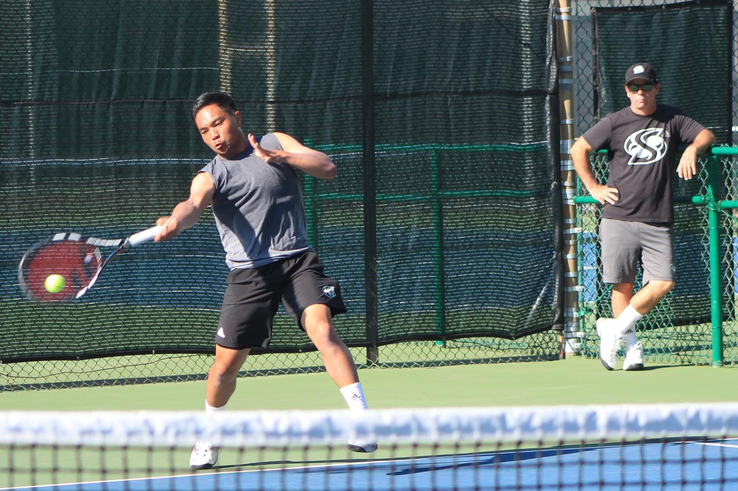 Sacramento State men's tennis coach Kevin Kurtz, right, oversees sophomore Hermont Legaspi, left, as he forehands the ball back to a teammate during practice at the Sacramento State Courts on Wed., March 7, 2018.