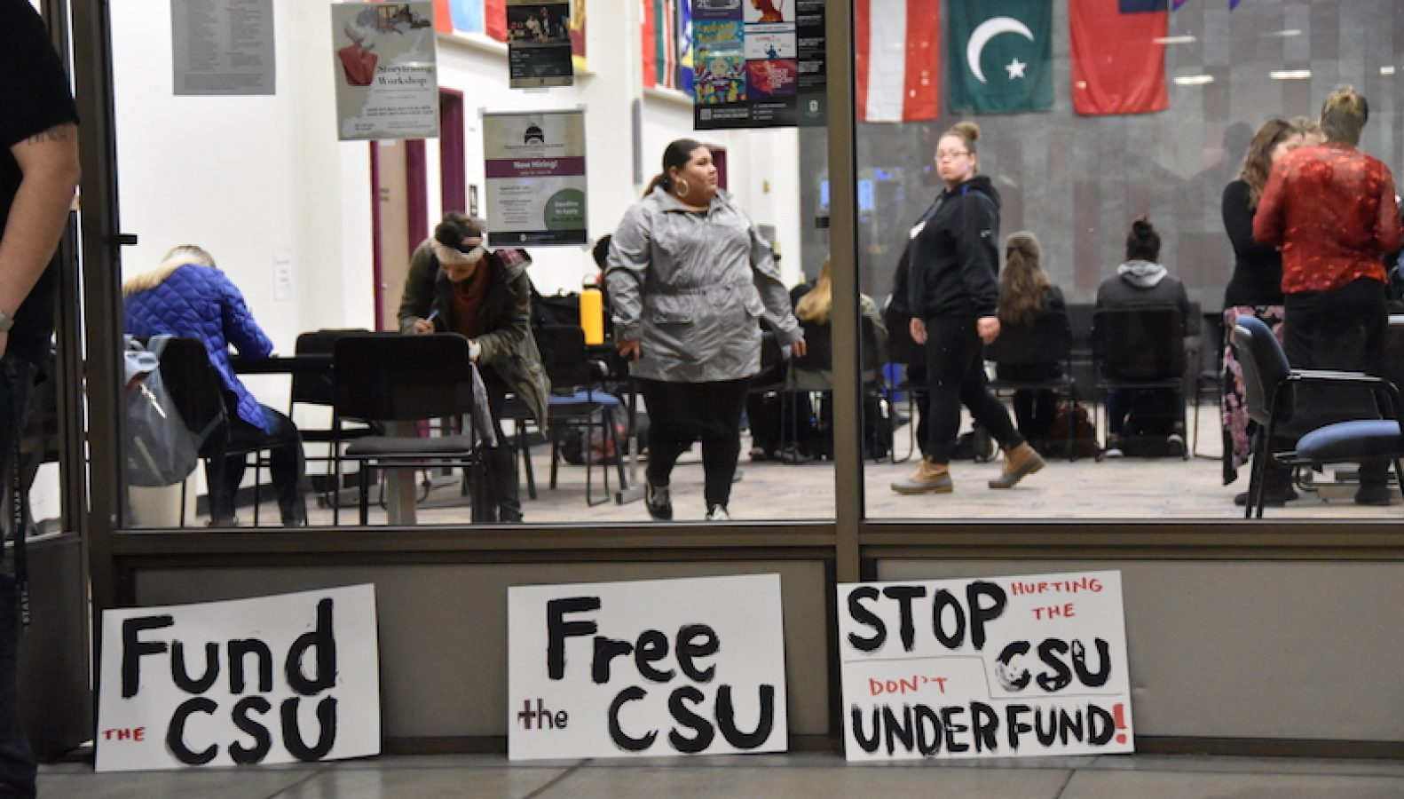 Signs left outside the Global Lounge by the SQE during a roundtable discussion on Tuesday. The students, faculty, and administration discussed the CSU funding gap, the upcoming tuition hike, and student insecurity. Photo by Vincent Moleski – The State Hornet