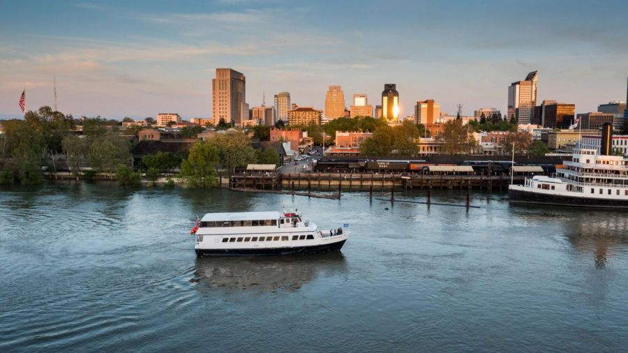 A Hornblower cruise ship moves past downtown Sacramento.