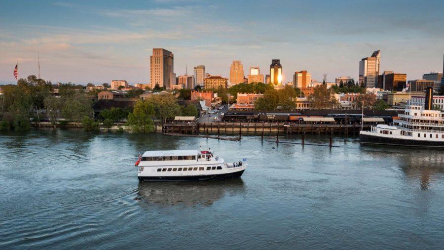 A Hornblower cruise ship moves past downtown Sacramento.