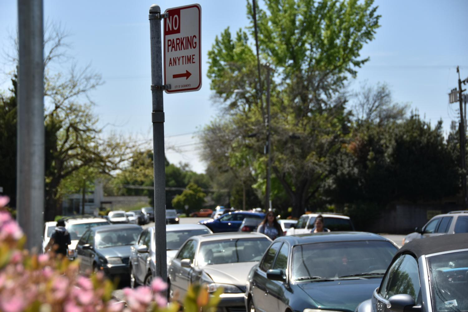 A 'No Parking' sign on Newman Court flanked by parked cars. Parking is legal anywhere behind the sign unless otherwise marked for emergency fire response or loading zones.