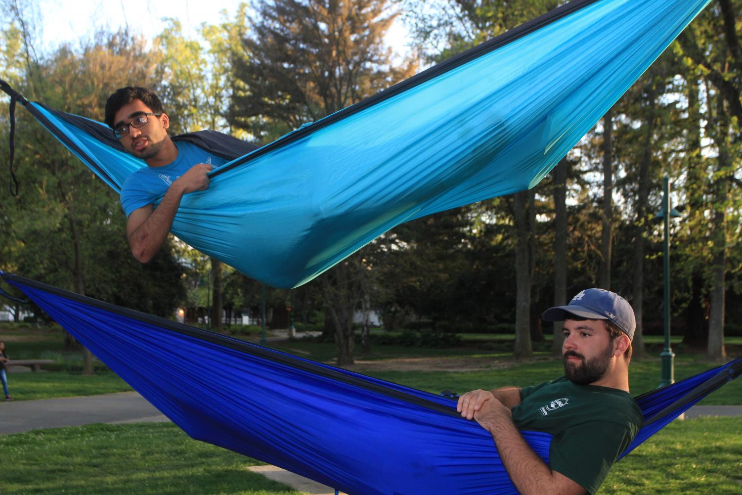 Computer science major Armaiz Adenwala, top, and business finance major and Hammock Club President Trent Simonson, bottom, engage with other members of Hammock Club at a Monday evening meeting on April 2, 2018 in grouping of trees between Riverfront Center, Lassen Hall and the bus stop. Hammock Club meetings are held Monday and Thursday evenings, and are open to all students.