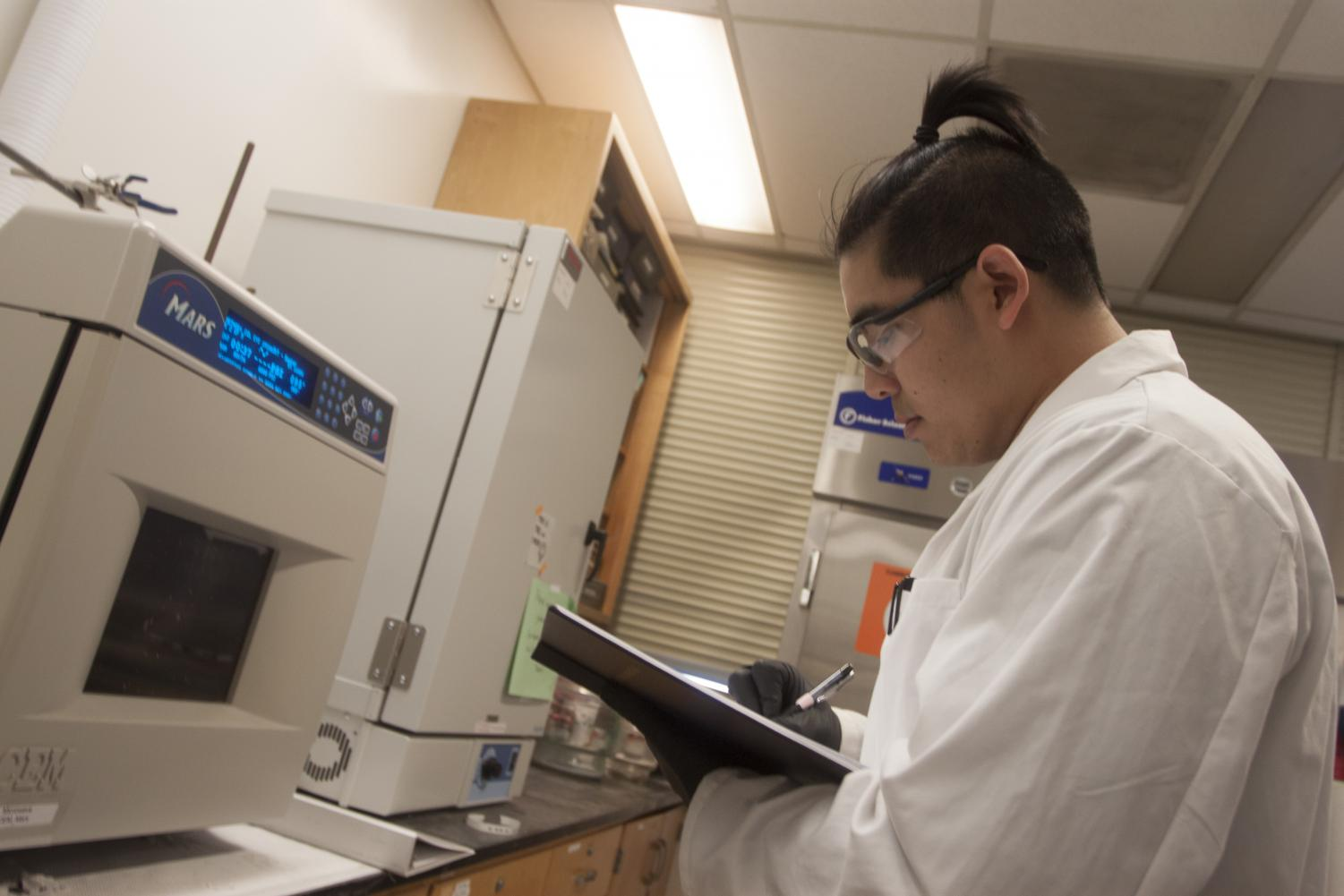 Biochemistry major Kevin Tran uses the microwave in a laboratory on the fifth floor of Sequoia Hall on April 19, 2018 to break down molecules. Tran is working with professor Katherine McReynolds on a project that may yield a topical medicine aimed at preventing the spread of HIV.