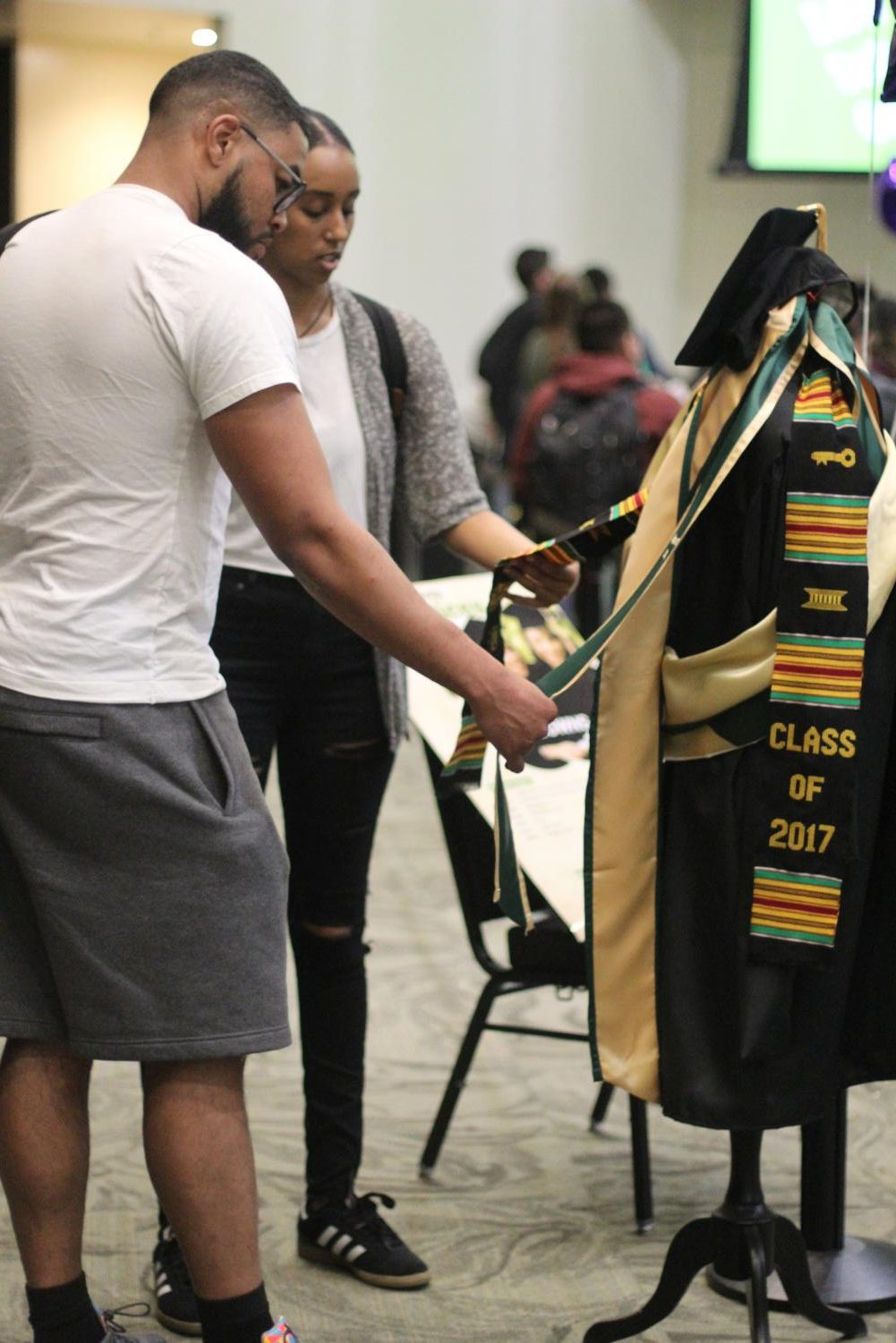 Seniors Tender Cooksie, left, and Yosan Zeweldi look at sashes to wear for graduation at Grad Fest on March 28, 2018.