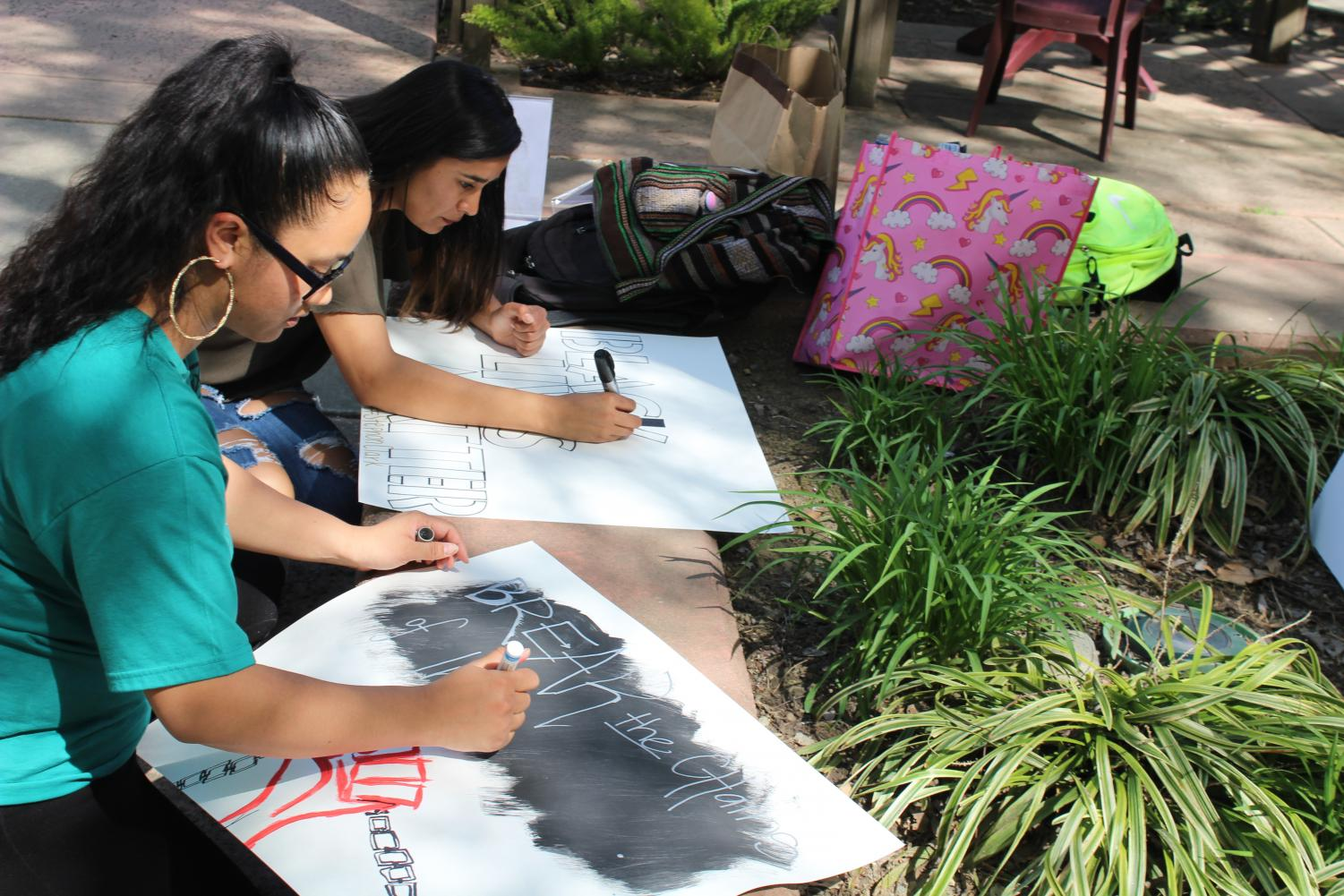 Sacramento State students Monica Linhthasack (closest) and Vanessa Trejo creating posters on Thursday March 29 in preparation for the event Linhthasack organized that will take place on April 3. Linhthasack's goal is