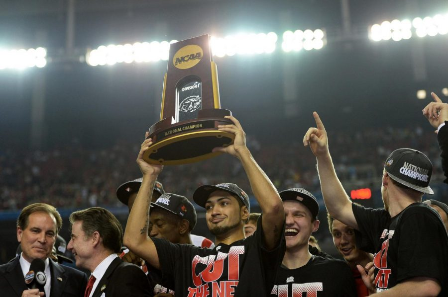 Louisville+point+guard+Peyton+Siva+holds+up+the+winning+trophy+after+his+team+won+the+Division+I+NCAA+men%27s+basketball+championship+in+2013.+The+title+has+since+been+vacated+after+the+program+was+discovered+to+have+committed+multiple+recruitment+violations.