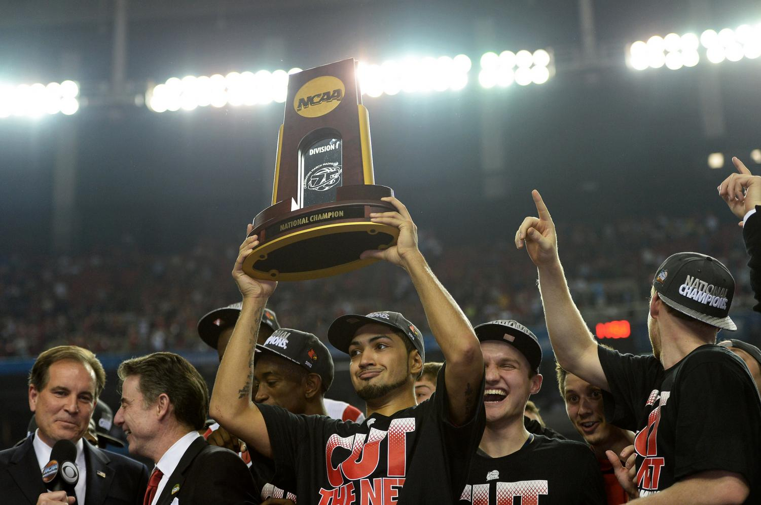 Louisville point guard Peyton Siva holds up the winning trophy after his team won the Division I NCAA men's basketball championship in 2013. The title has since been vacated after the program was discovered to have committed multiple recruitment violations.