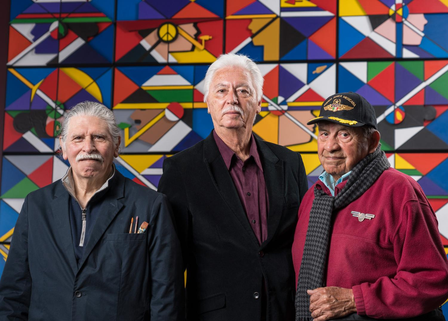 RCAF members Juanishi Orosco, left, Stan Padilla, and Esteban Villa pose in front of the lower panel of their mural.