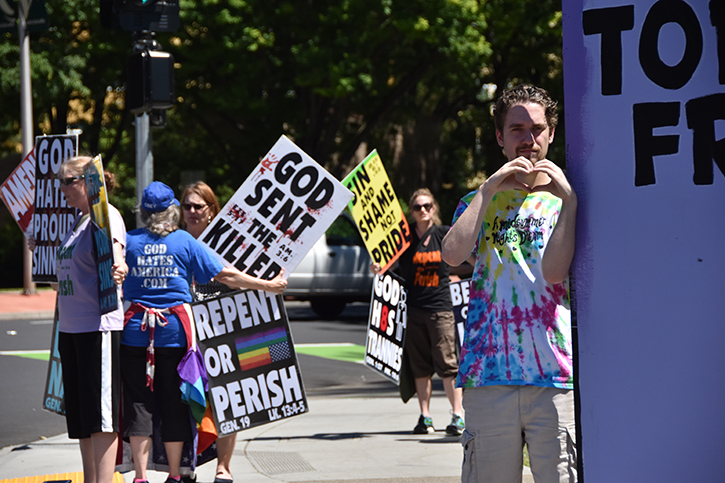 Liam Worrell-Olson, right, makes a heart with his hands while standing in front of picketers from the Westboro Baptist Church, who protested at the J Street entrance to Sac State on Tuesday, May 8. The Westboro Baptist Church is a Kansas-based Christian fundamentalist group known for its inflammatory anti-LGBT speech.