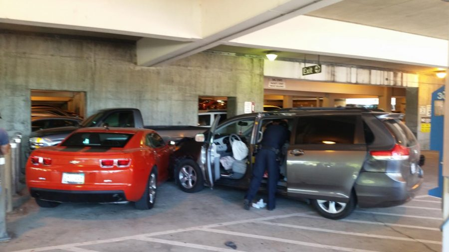 Police examine the stolen van that crashed into two parked cars in Parking Structure I. The driver got out and hid underneath a car before being apprehended according to police.
