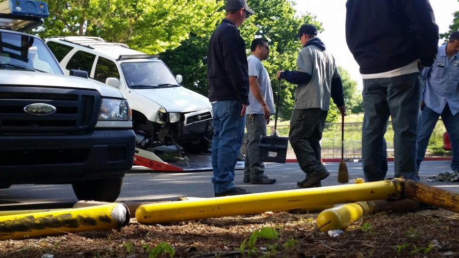 A facilities management crew stands in front a pile of damaged guard rails after a driver collided with them and a fire hydrant on Thursday morning. The driver was arrested for driving under the influence according to Sgt. Jeff Reinl of Sacramento State Police.
