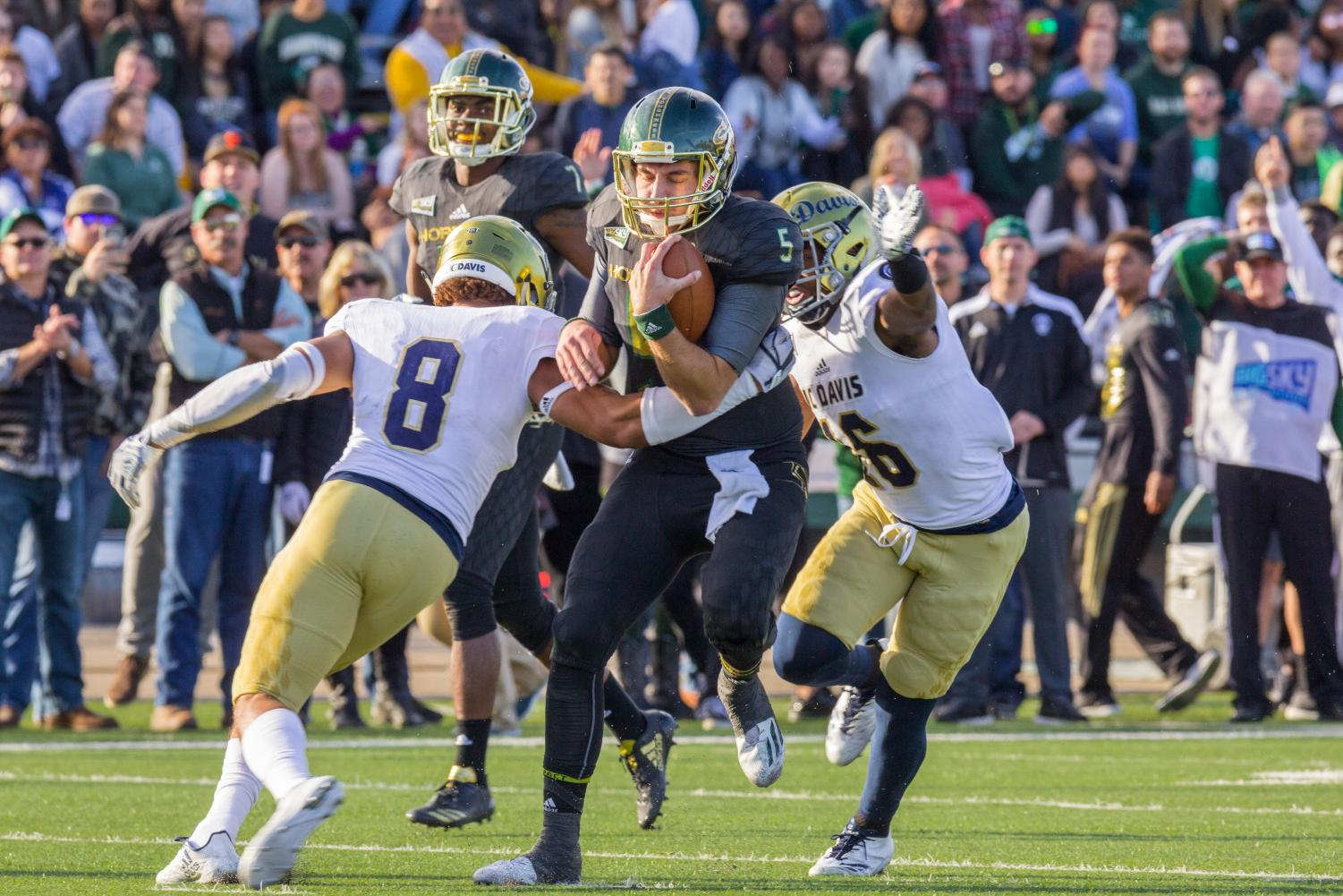 Sacramento State junior quarterback Kevin Thomson, middle, is tackled down by two UC Davis defenders in the 64th annual Causeway Classic at Hornet Stadium on Saturday, Nov. 18, 2017. Sac State defeated the Aggies 52-47.