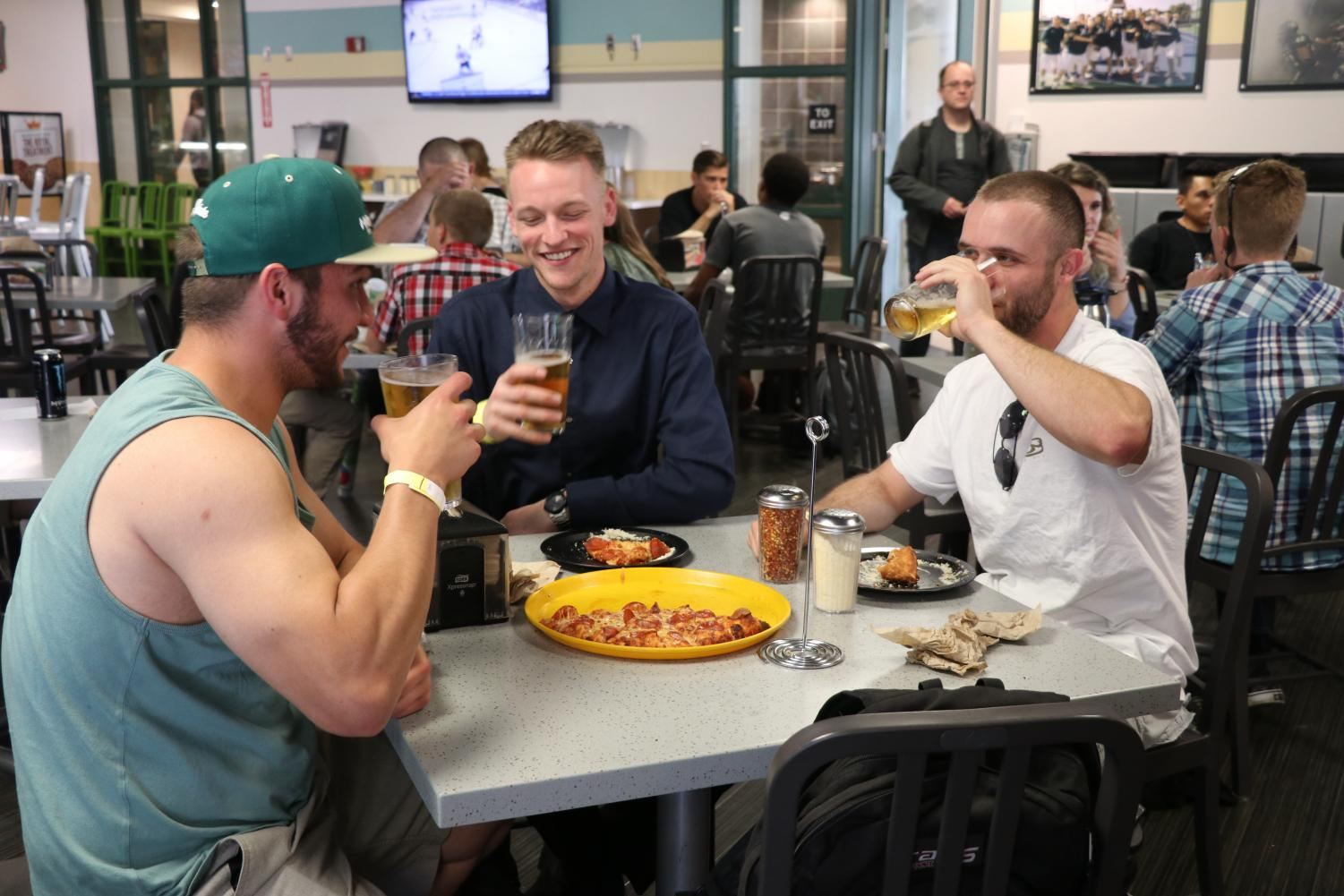 Aaron Jestice, Parker Wright and Kevin Khouri eat pizza and drink beers at Round Table Pizza on Sacramento State's campus, Thursday, May 3, 2018.
