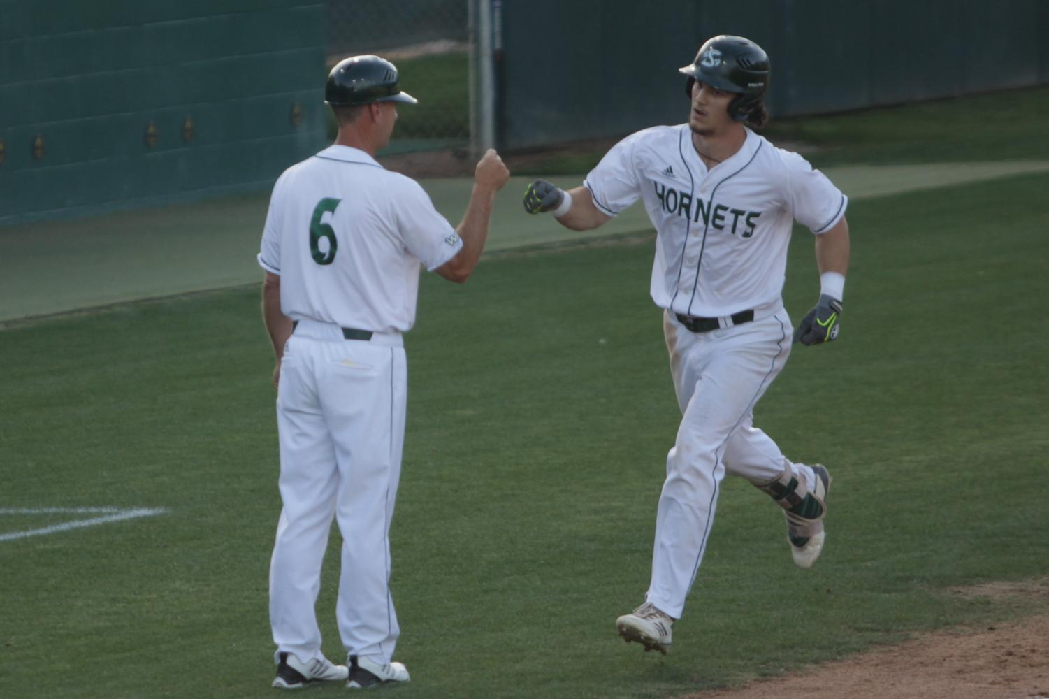 Sacramento State junior outfielder James Outman, right, celebrates with Sac State coach Reggie Christiansen, left, after Outman hit a home run against Seattle University on Saturday, May 5, 2018 at John Smith Field. Outman was selected by the Los Angeles Dodgers in the seventh round of the 2018 MLB Draft