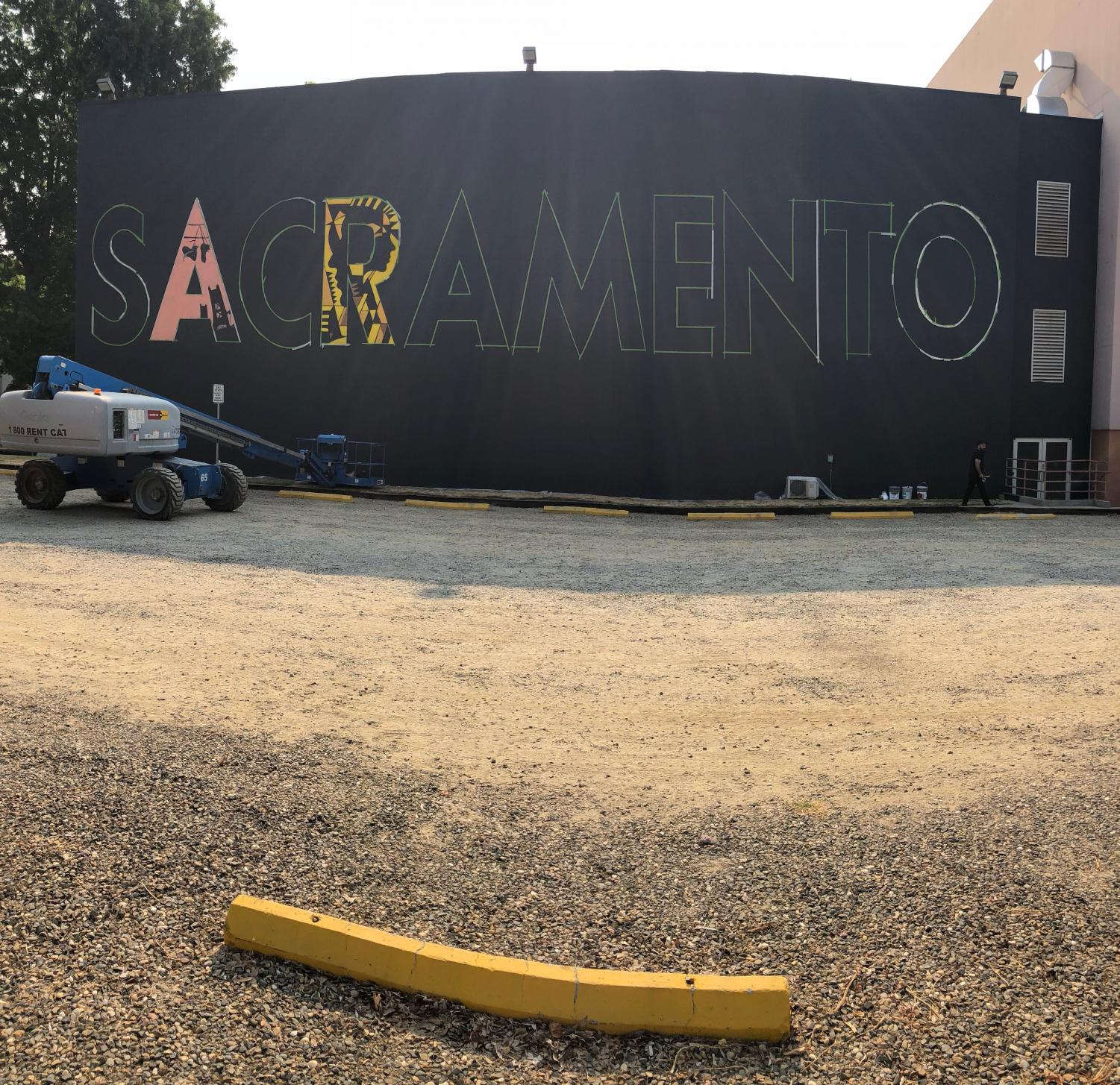 Raphael Delgado and nine other artists are completing this 'SACRAMENTO' mural on the side of Shasta Hall as part of the Wide Open Walls art festival that is being held from Aug. 9-19.