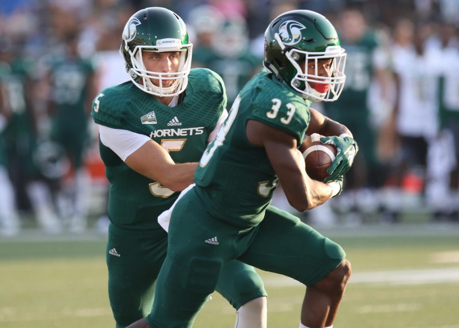 Senior quarterback Kevin Thomson hands the ball off to sophomore running back Elijah Dotson (33) who scored a 73-yard touchdown to open the scoring for Sacramento State in its 55-7 win over St. Francis (IL.) on Sept. 1 at Hornet Stadium.