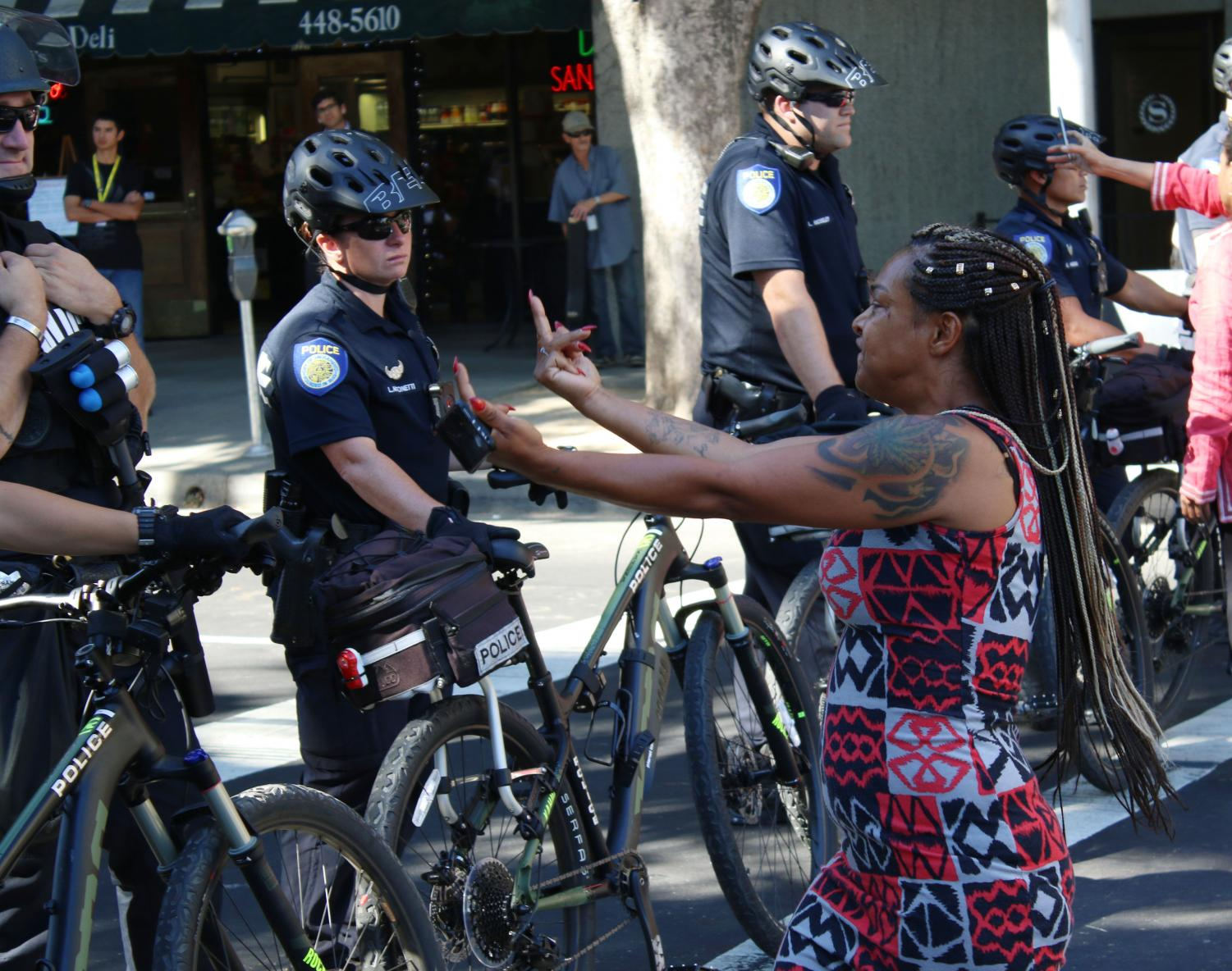 Brandy+Bains-Wood%2C+a+Sacramento+native%2C+flips+off+police+standing+guard+on+the+intersection+of+J+St.+and+13th+St.+on+Tuesday%2C+Sept.+18.+Black+Lives+Matter+protesters+were+demonstrating+outside+a+CopWest+Training+and+Expo.