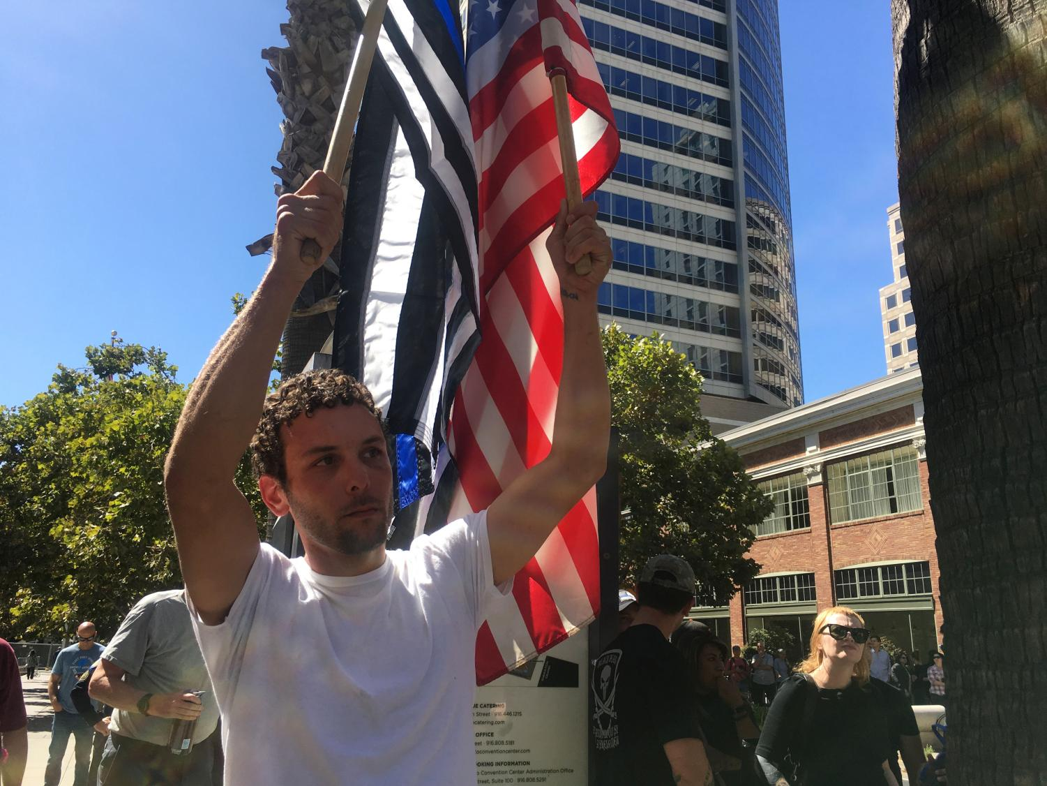Sacramento+resident+Matthew+Long+waives+an+American+flag+and+Blue+Lives+Matter+flag+during+the+Cop+Expo+Shut+Down+at+the+Sacramento+Convention+Center+Tuesday%2C+Sept.+18.+Long+said+he+was+there+in+honor+of+friend+Sacramento+County+Sheriff%27s+Deputy+Mark+Stasyuk+who+was+shot+and+killed+Monday%2C+Sept.+17+while+on+duty.+
