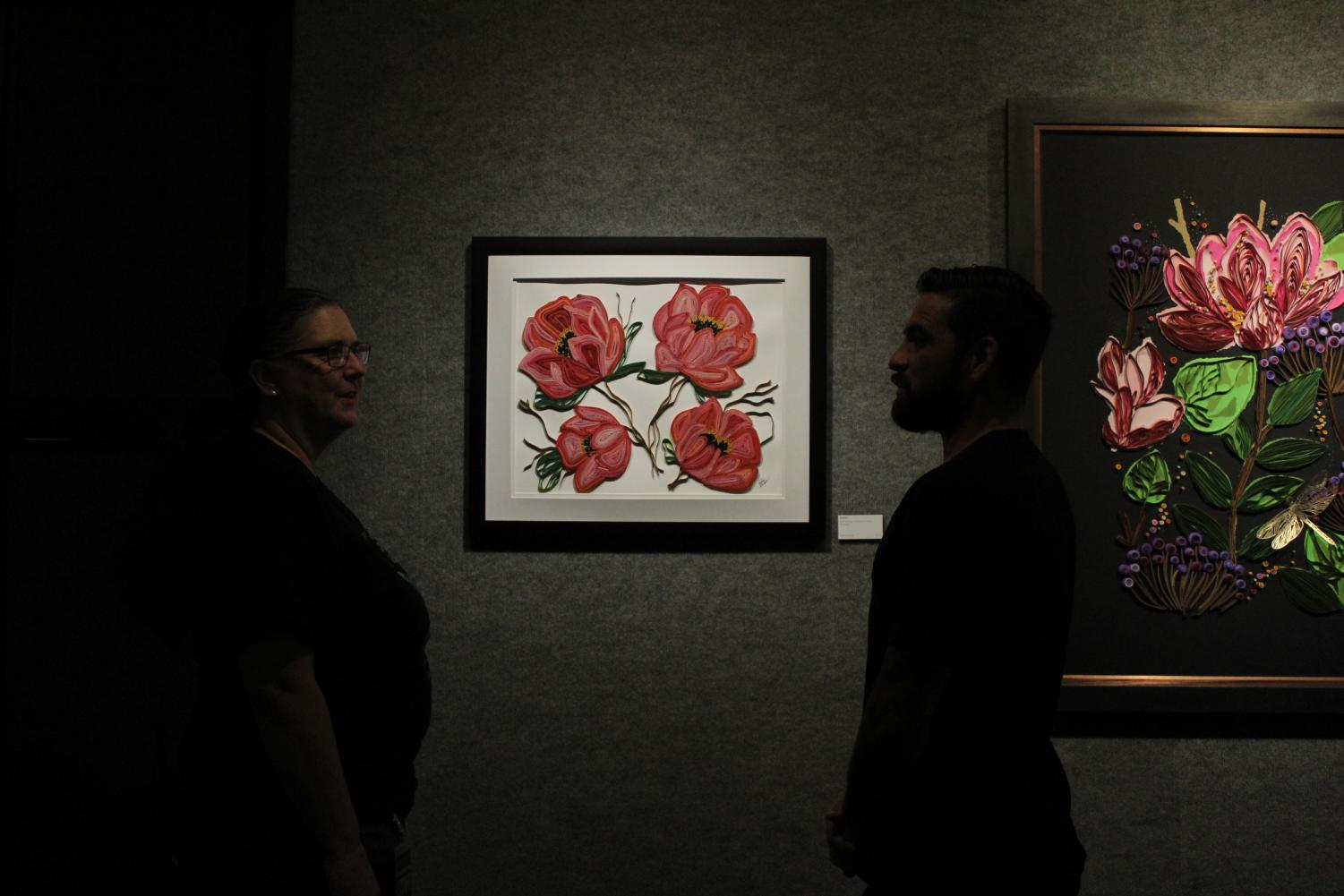 Rebecca Dietzler (left) and Gabriel Alarcon (right) discuss a floral piece at the Spring Delusions exhibit in the University Union's art gallery on Sept. 6