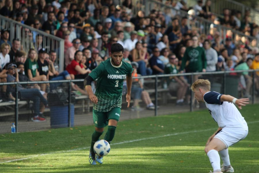 Sacramento State Hornets junior defender Abraham Rosales attempts to dribble past UC Davis Aggies sophomore defender Jacob Rudolph during the second half the game Oct. 27.