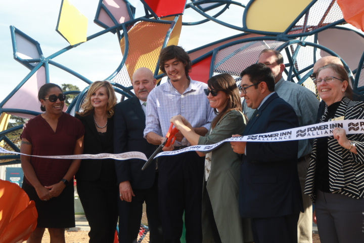 Sacramento+State+student+artists+Chris+Duffy+and+Tiffany+Boddeker+are+surrounded+by+school+administrators%2C+faculty+and+city+councilmen+as+they+cut+a+ribbon+Friday%2C+Nov.+2%2C+2018+at+the+unveiling+of+%22%23Poppy%2C%22+a+16-foot+steel+sculpture+of+a+stegosaurus+they+created+as+a+public+art+project.+