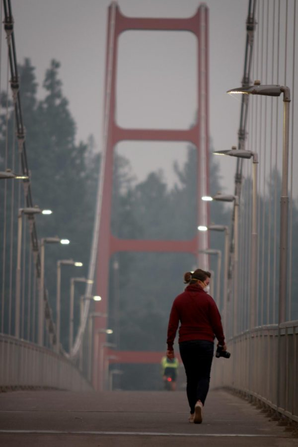 Danielle+Knapp%2C+a+collections+manager+at+University+of+California%2C+Davis%2C+walks+across+the+Guy+West+Bridge+to+take+photos+of+the+smoky+atmosphere+at+Sacramento+State+on+Nov.+14.+Both+Sac+State+and+UC+Davis+campuses+were+closed+Wednesday+due+to+poor+air+quality+from+the+Camp+Fire+burning+in+Butte+County.