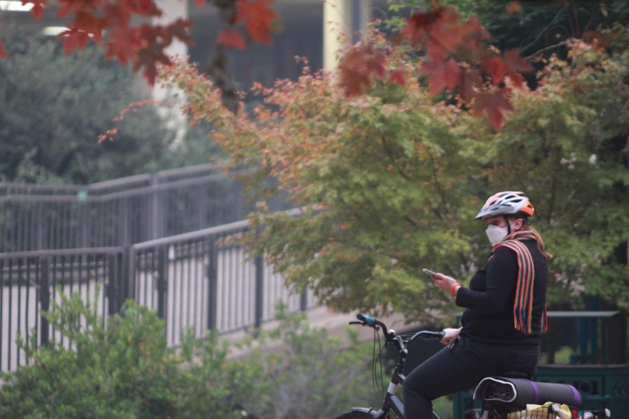 A+female+biker+stops+in+front+of+the+Sacramento+State+library+to+take+photos+of+the+smoke-filled+closed+campus+on+Nov.+14.+