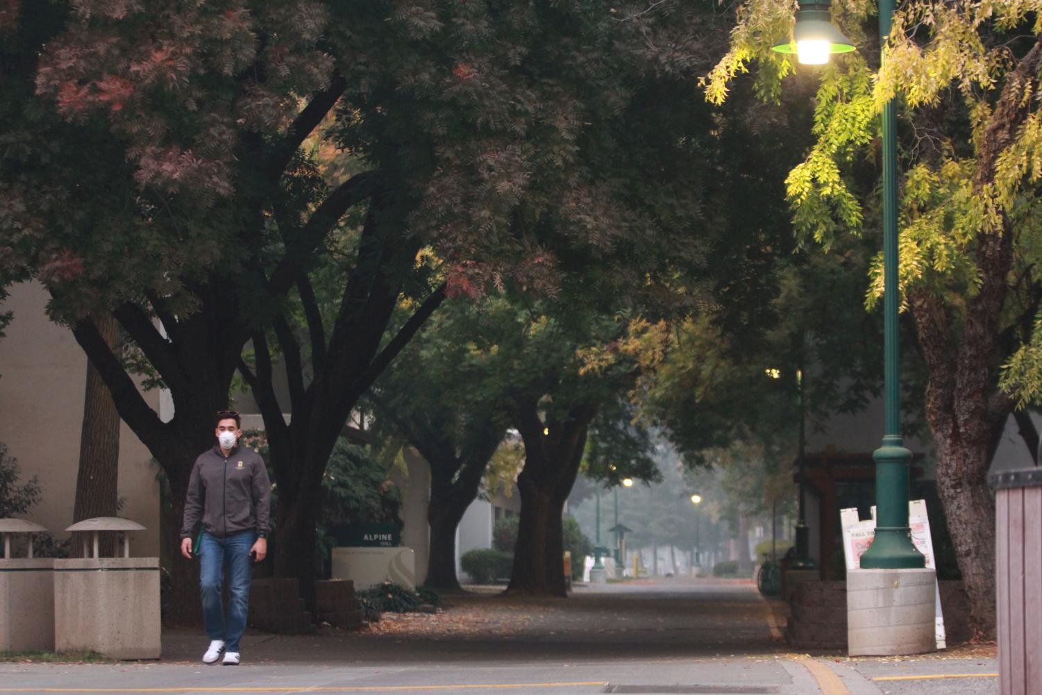 Sacramento State Residence Life Coordinator Edgardo Palomo wears a respirator mask as he treks through the smoke-filled campus walkways on Nov. 14. President Robert Nelsen announced for the third day in a row that campus will be closed Thursday due to the poor air quality from the smoke of the Camp Fire in Butte County.