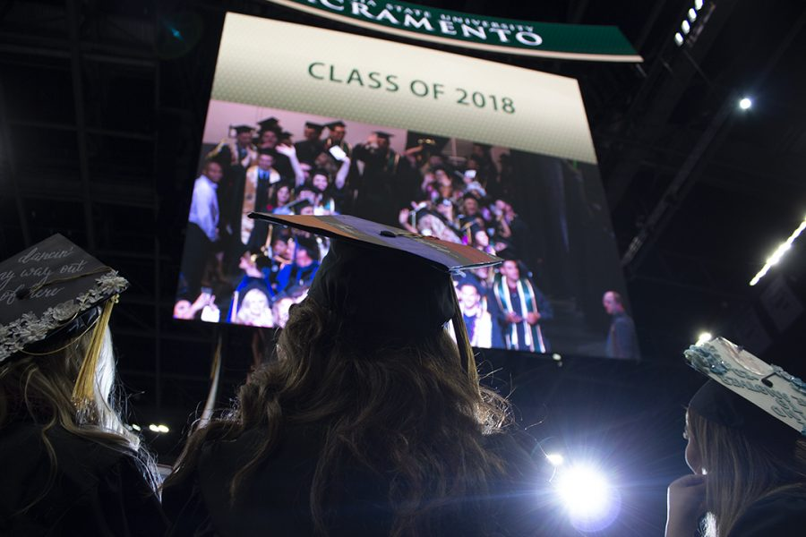 Graduating Sacramento State students look up at themselves on a jumbotron inside the Golden 1 Center during the spring commencement ceremony on May 18, 2018. Multiple Sac State departments will be making changes to the names of their majors in the 2019-2020 school year.