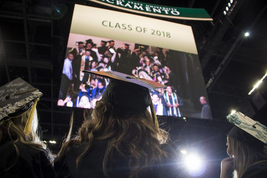 Graduating Sacramento State students watch themselves on a giant screen inside Golden 1 Center during the commencement procession May 18, 2018 in Sacramento, Calif.