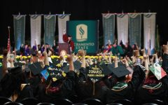 Students attending the Spring 2018 commencement ceremony held at Golden 1 Center join Sacramento State President Robert Nelsen in a 'Stingers up' salute after his address on May 18, 2018.  Nelsen announced an on-campus, drive-through commencement for the 2020 and 2021 graduating classes Monday in a SacSend email.