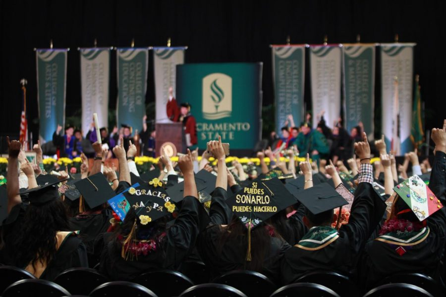 Students+attending+the+Spring+2018+commencement+ceremony+held+at+Golden+1+Center+join+Sacramento+State+President+Robert+Nelsen+in+a+%E2%80%98Stingers+up%E2%80%99+salute+after+his+address+on+May+18%2C+2018.++Sacramento+State+sent+an+email+survey+to+graduating+seniors+Wednesday%2C+giving+them+the+option+to+choose+how+likely+they+would+be+to+attend+three+graduation+possibilities%3A+on+campus%2C+drive-thru+or+virtual+commencement.+