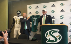 Sac State Athletic Director Mark Orr (left) and new Sac State football coach Troy Taylor hold up a jersey at Taylor's introductory press conference Dec. 18 at Broad Fieldhouse.