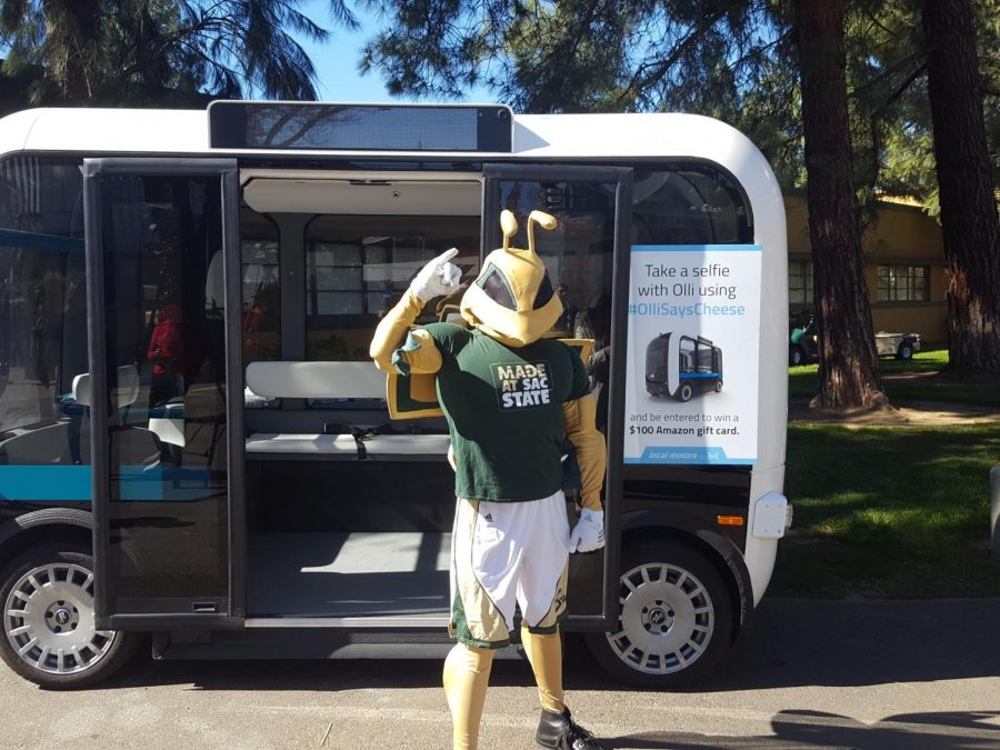 Sac State's mascot Herky poses with a driverless vehicle named Olli at a press conference at the Nest Thursday. Two Olli vehicles will start giving students rides around campus Friday.