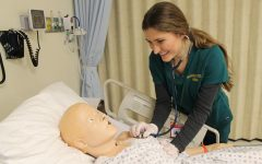 Nursing student, Danielle Baldwin, using a stethoscope on a realistic simulation mannequin in one of Sacramento States laboratories in Folsom Hall. Simulation labs allow nursing students to gain essential skills and a