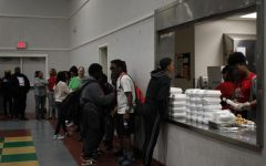 Attendees for the summit stand in line for a free meal courtesy of The Rose Family Creative Empowerment Center during the Stephon Clark Legacy Weekend in Meadowview Friday. They work to aid vulnerable youth throughout the Sacramento area and worked with the Clark family to organize the summit.