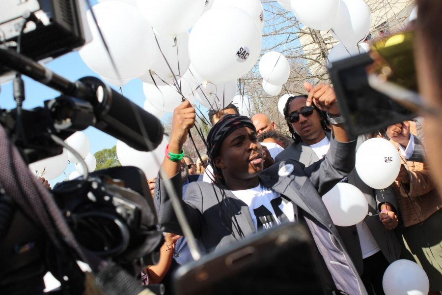 Stevante Clark, Stephon Clark's older brother, holds a set of balloons aloft during a balloon release ceremony held immediately after a service at Genesis Church in Meadowview on Monday. The service was part of the one-year anniversary remembrance of unarmed 22-year-old Clark, who was shot and killed by Sacramento Police on March 18, 2018.
