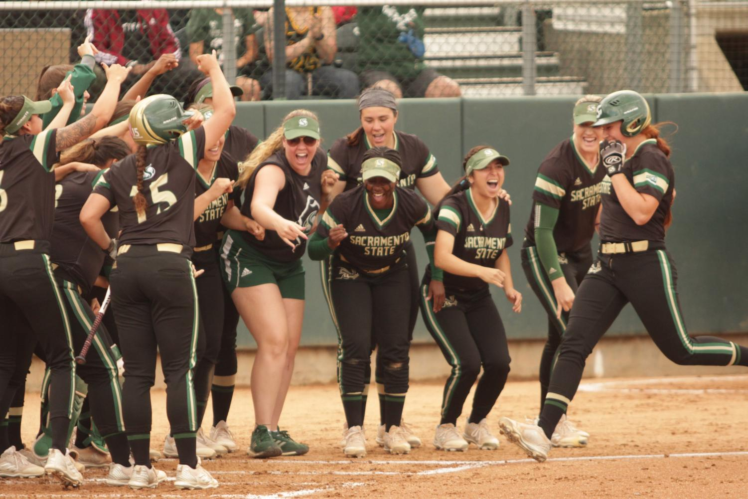 The Sacramento State softball team celebrates with sophomore outfielder Suzy Brookshire, right, after she hit a home run against the University of North Dakota at Shea Stadium on Saturday, April 28, 2018. The Hornets defeated North Dakota 4-1.