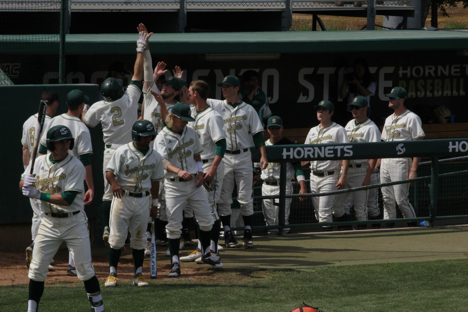 Sac State senior outfielder Bronson Grubbs (#2) jumps and high-fives teammate, junior right-handed pitcher Austin Roberts, after scoring a run in a 5-3 loss to UT Rio Grande Valley Sunday at John Smith Field. Grubbs had one hit, one RBI and one run scored in the loss.