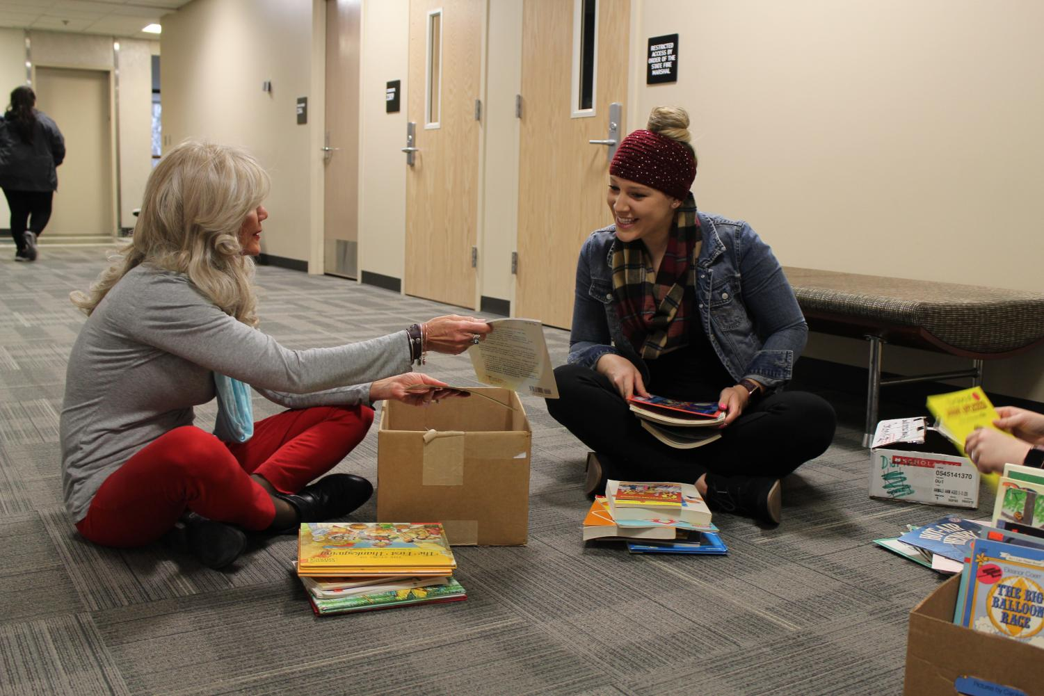 Professor Celeste Roseberry-McKibbin and Sac State communication sciences and disorders major Marisa Dix sit on the floor at Folsom Hall counting and sorting through book donations. Dix has been helping Roseberry-McKibbin for about a year after hearing about Roseberry-McKibbin's Love Talk Read program during one of her classes.
