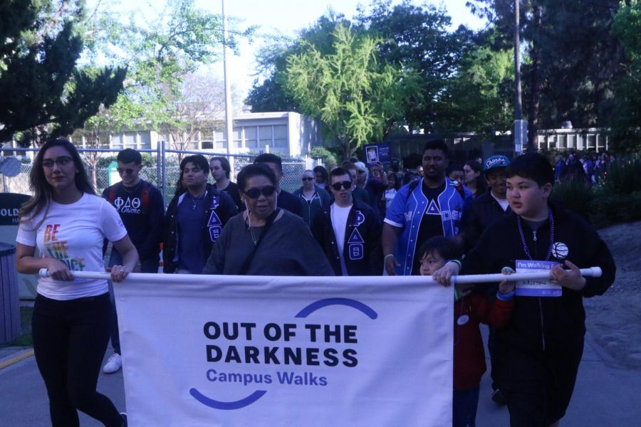 Participants in Sac State's eighth annual Out of the Darkness walk by Humboldt Hall on April 11, 2019.  Participants walked two miles around campus to bring awareness to suicide prevention.