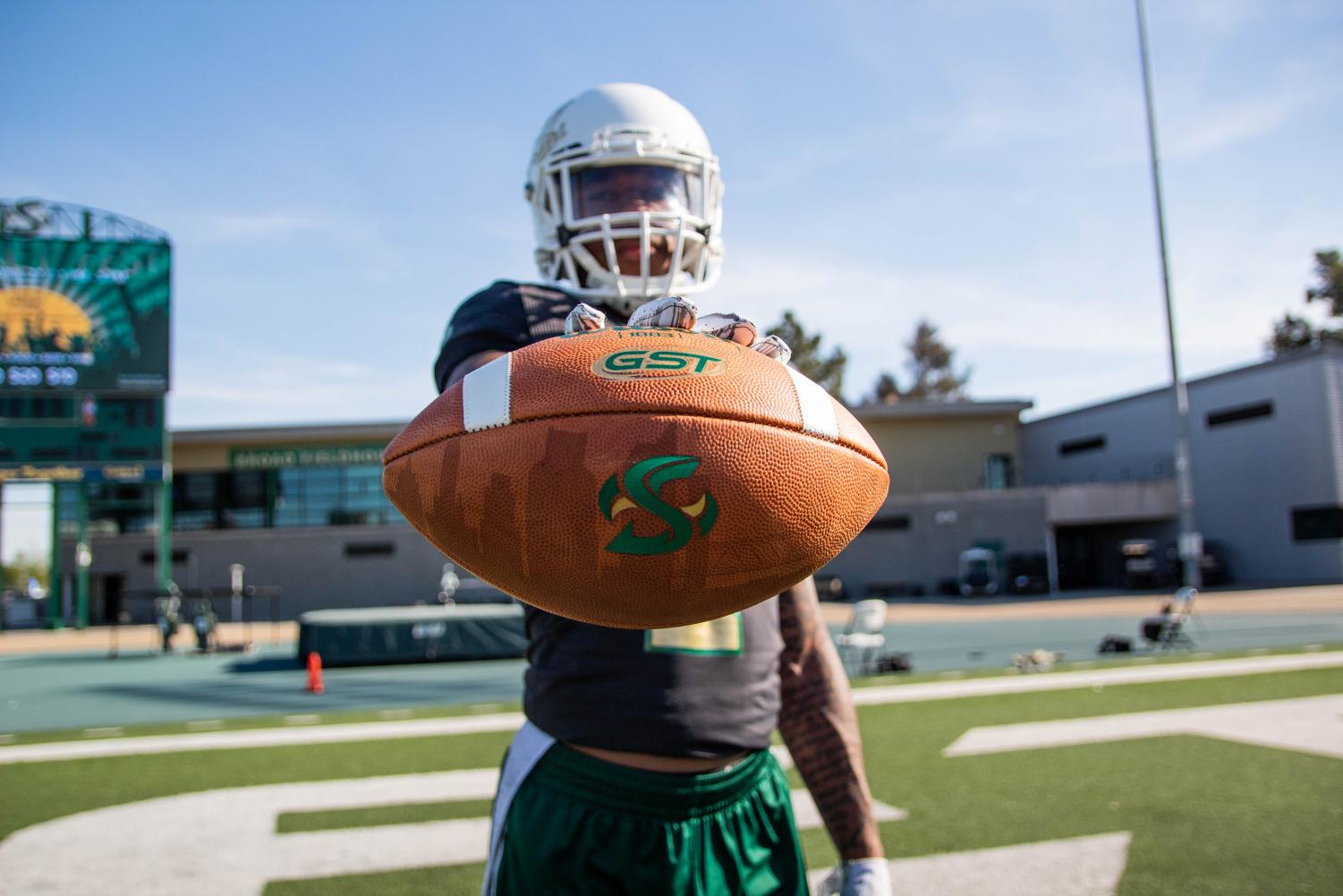 Sac+State+senior+safety+Mister+Harriel+poses+with+a+football+April+18+at+Hornet+Stadium.+Harriel+is+hopeful+to+be+selected+in+the+2019+NFL+Draft.+