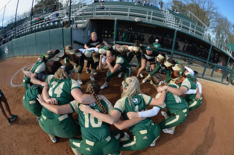 Sac+State%27s+softball+team+huddles+around+sophomore+outfielder+Charizma+Guzman+as+she+hypes+the+team+up+during+a+pre-game+ritual.+The+team+has+many+superstitions%2C+from+some+players+braiding+their+hair+a+certain+way%2C+to+never+touching+the+foul+line+as+they+leave+the+field.+