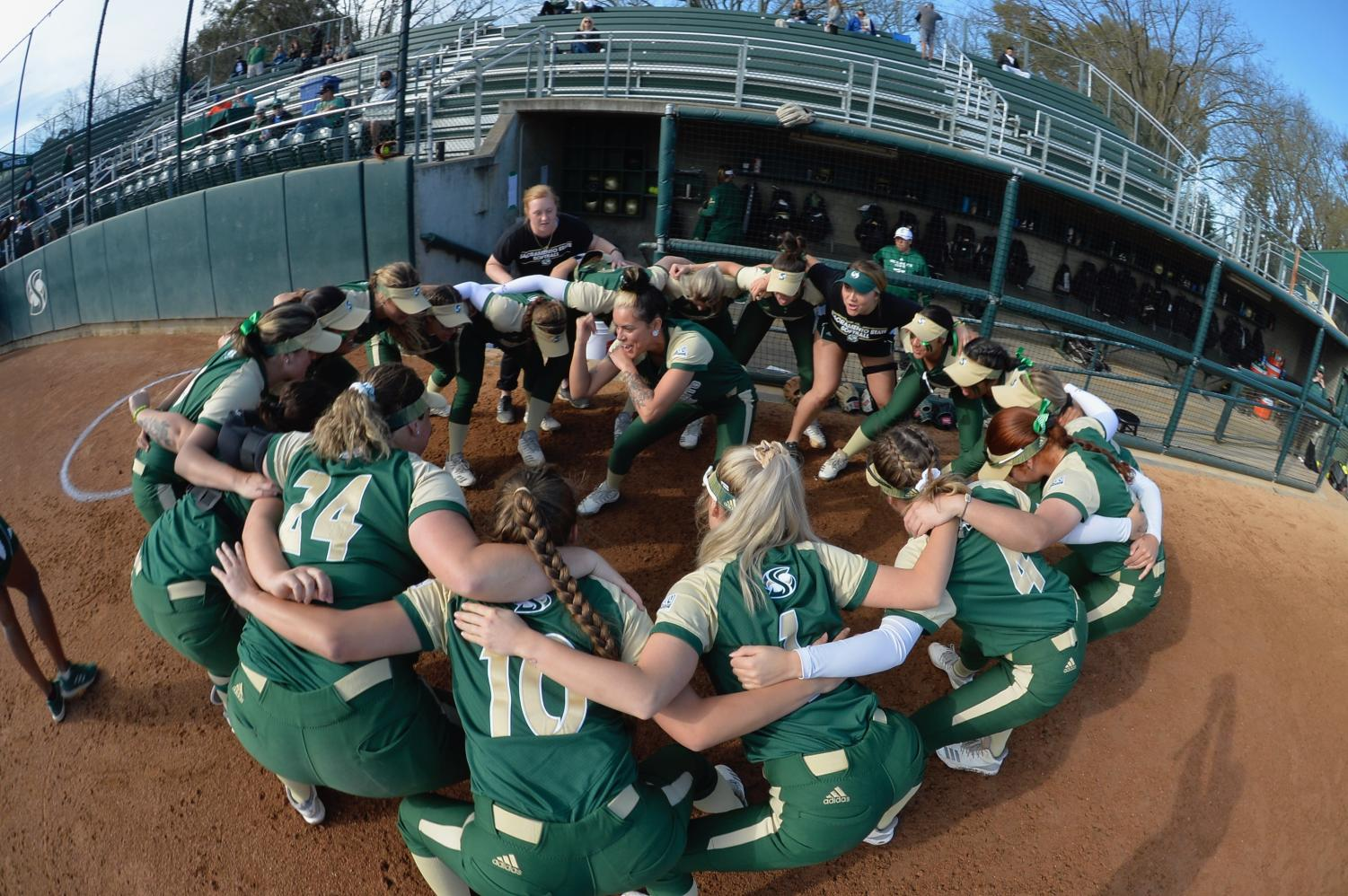 Sac State's softball team huddles around sophomore outfielder Charizma Guzman as she hypes the team up during a pre-game ritual. The team has many superstitions, from some players braiding their hair a certain way, to never touching the foul line as they leave the field.