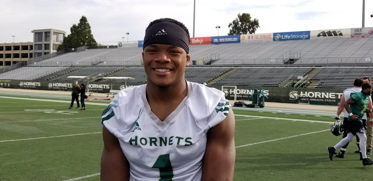 Junior running back Elijah Dotson smiles as spring football practices begins around him. As a sophomore in 2018, he led the team in rushing with over 1,000 yards.